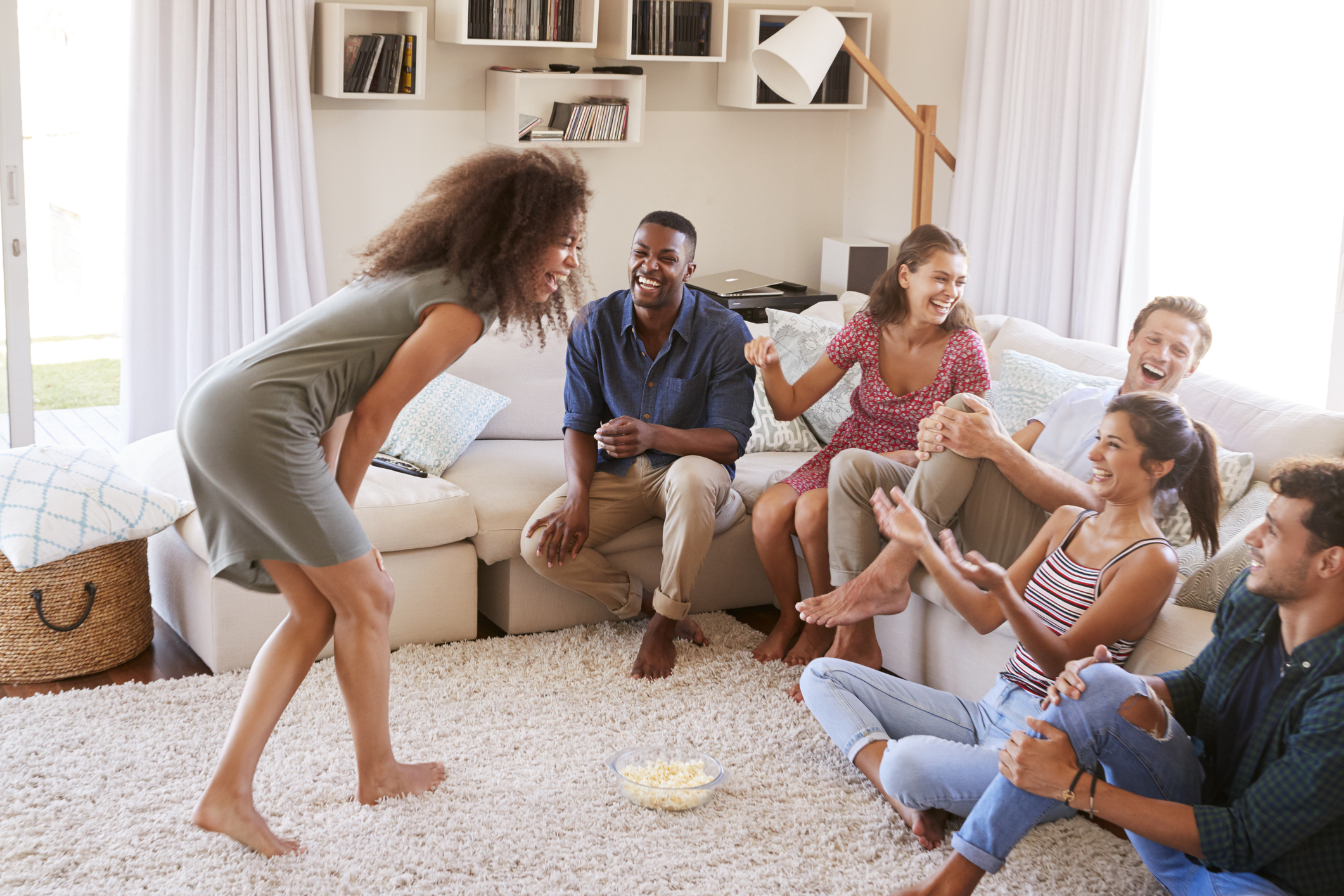 Group Of Friends in apartment Having Fun Playing Charades Together