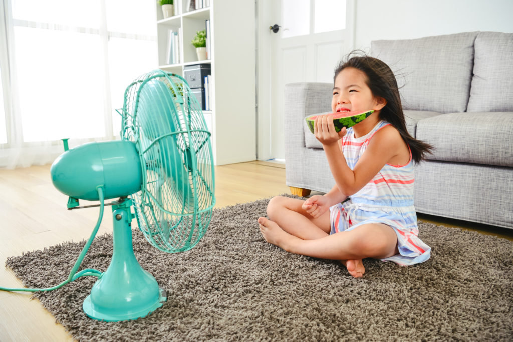 little girl eating watermelon in front of fan in cool apartment